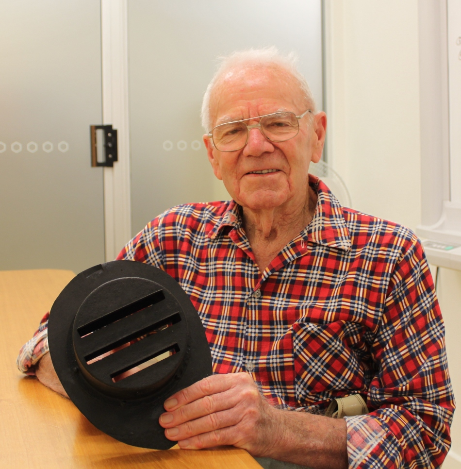 Clive Read holding automobile headlight cover c.1939. Used to subdue light from Read family milk van during blackouts and brownouts in World War II.